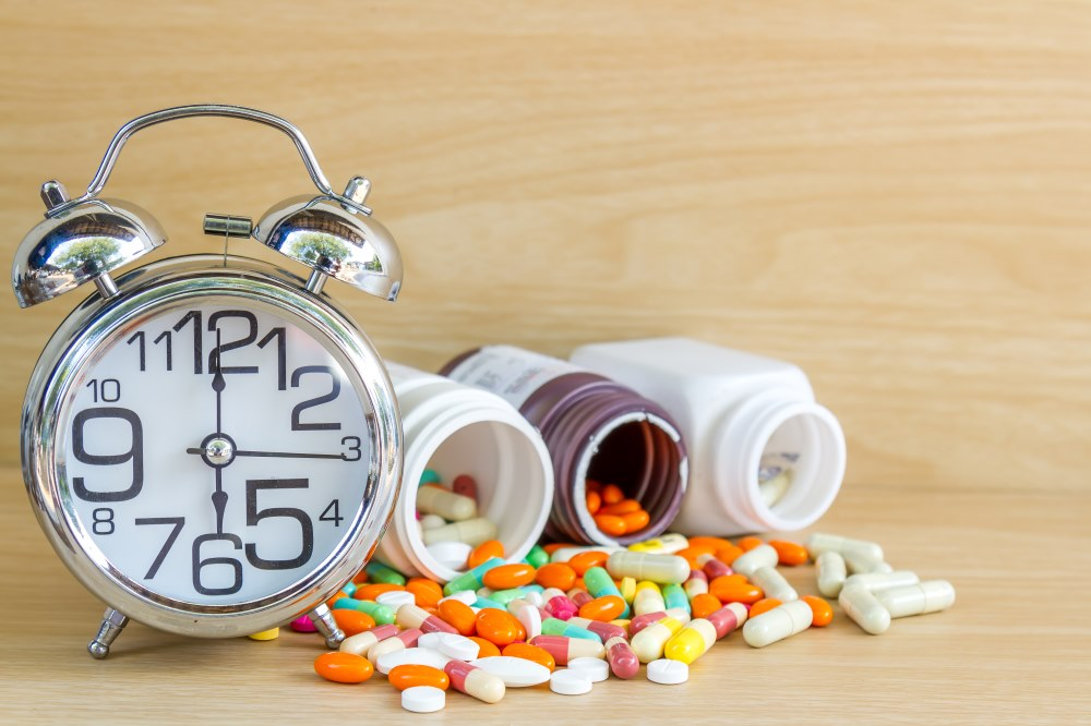 Medicine pill and capsule. Clock shows 6 am or pm