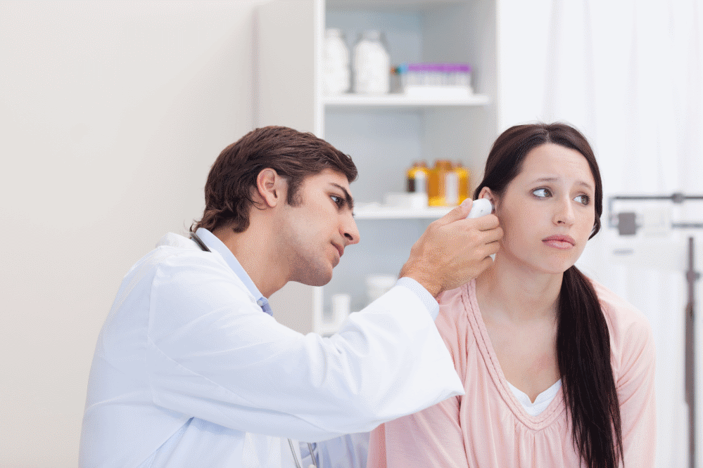 Male doctor examing the ear of female patient
