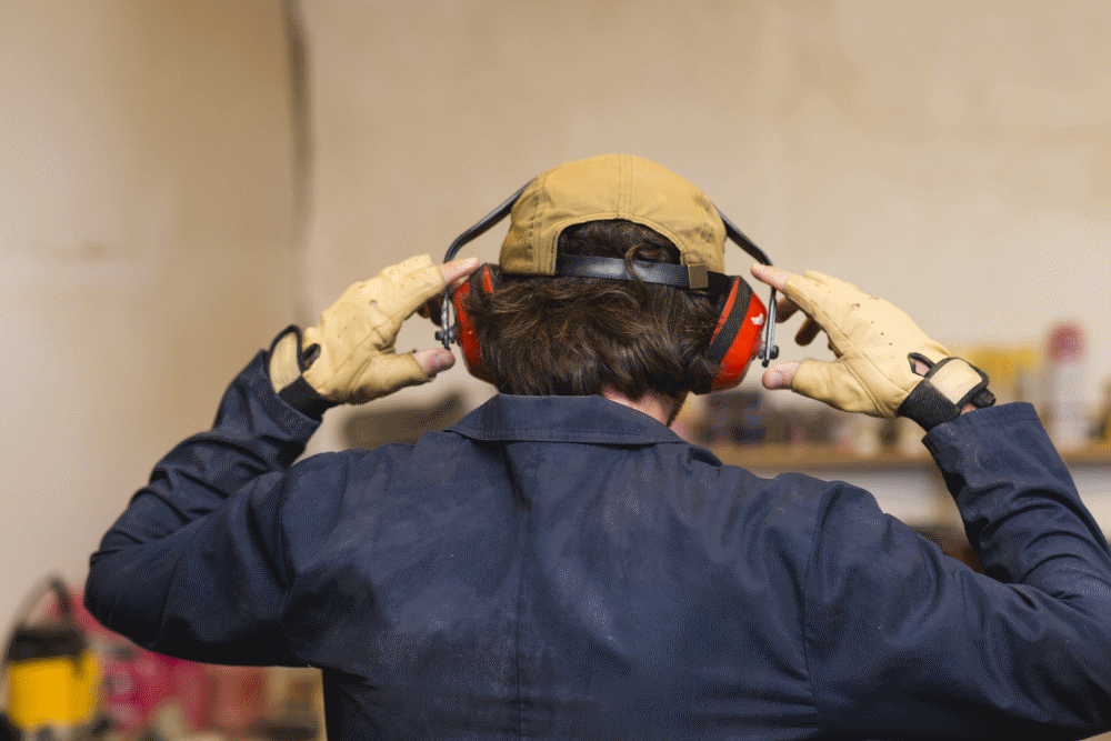 Man working at a noisy place protecting his ears